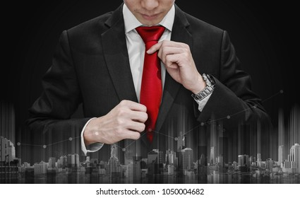 Businessman tying red necktie and raising graph diagram with building technology. Business growth and investment