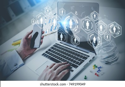 Businessman typing at his laptop and holding a smartphone. Office with a network HUD sketch. Toned image double exposure mock up Elements of this image furnished by NASA