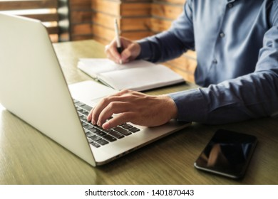Businessman typing in information on a laptop or browsing the internet as he makes notes in a journal on the desk