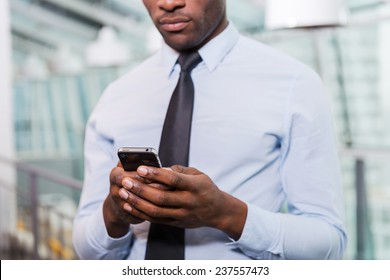 Businessman typing message. Cropped image of young African man in shirt and tie texting on his mobile phone while standing indoors