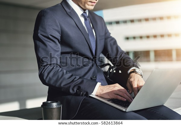 Businessman typing on his laptop. Horizontal indoors shot