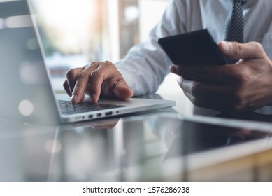 Businessman typing on laptop computer keyboard and using mobile smart phone with digital tablet on desk. Business man connecting internet, networking in modern office, closeup