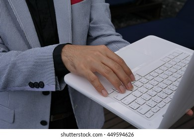 A businessman typing on laptop's keyboard