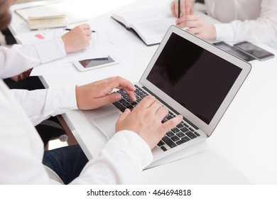 Businessman typing. Women taking notes. Smart phone on table. Concept of business meeting routine. Mock up