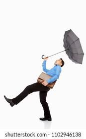 Businessman with umbrella and briefcase being blown away