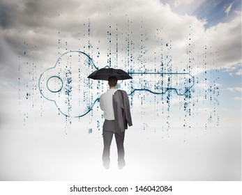 Businessman with an umbrella looking at a key with blue sky on the background