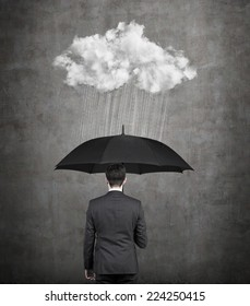 Businessman with umbrella protecting himself from the storm. A concept of protection from recession or economic crisis.