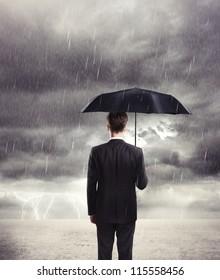 Businessman with umbrella in rain