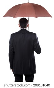 Businessman with umbrella. Rear view of mature man in formalwear holding umbrella while standing against white background