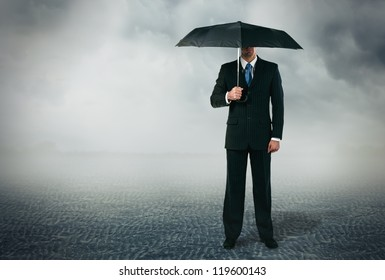Businessman with umbrella standing at cloudy background