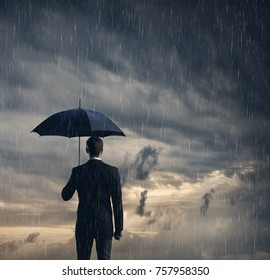Businessman with umbrella standing over dark, dramatic ocean background. Business, crisis, protection, concept.