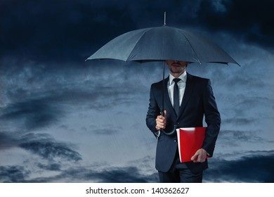 businessman with umbrella in stormy weather holding red folder