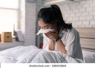 The businessman is unable to work, she is sick and sneezing heavily in bed.