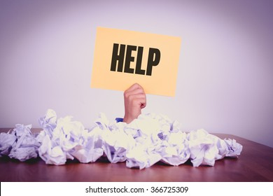 Businessman under crumpled pile of papers with hand holding a HELP Sign