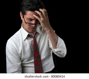 A businessman under intense stress ponders his job future at his office.