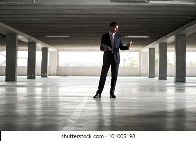 Businessman in underground parking holding tablet and mobile phone