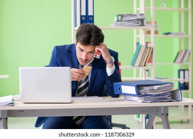 Businessman unhappy with excessive work sitting in the office