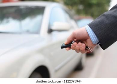 Businessman unlocking car using remote