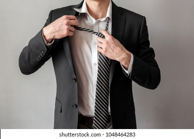 Businessman untying tie, business and work concept