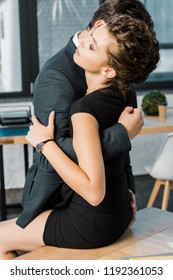businessman unzipping dress of seductive businesswoman at workplace in office