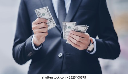 Businessman with US Dollar bills in his hand. Business and Finance concept