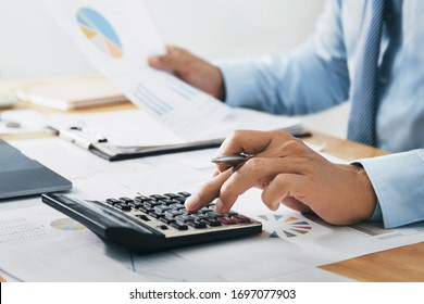 businessman use calculator and computer holding paper work with pen on desk in office. finance and accounting concept