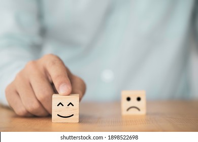 Businessman use finger to pointing smile face which print screen on wooden cube block , Emotion and mindset concept.