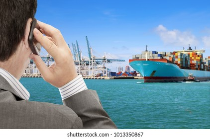 Businessman use smart phone for logistic business, in the background container terminal with cargo ship