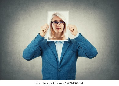 Businessman use a woman portrait as undercover, hiding his face behind photo sheet, like a fake mask. Private life, split personality and unreal identity concept.
