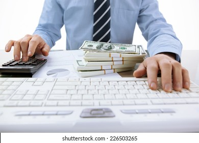 Businessman uses computing device, calculator / close-up photo of successful accountant working with computer keyboard in the office