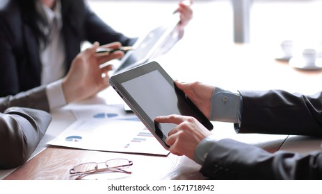 businessman uses digital tablet to check financial data