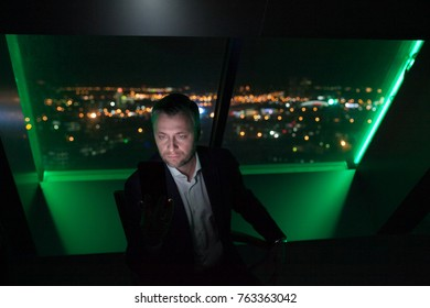 Businessman uses a smartphone sitting by the window in the office on a background of a night city.