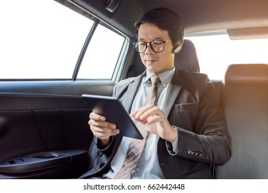 A businessman uses a tablet in a car.