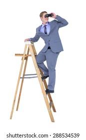Businessman using binoculars against a white background