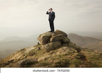 Businessman using binoculars on a rock in the mountains