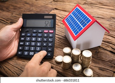 Businessman using calculator by coins and model home with solar panel on wooden table