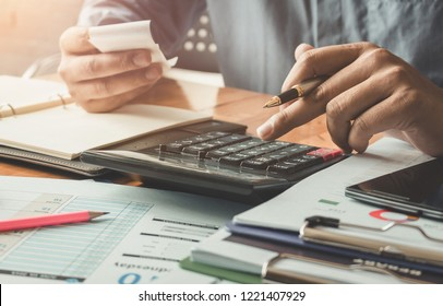 Businessman using calculator and calculate bills in office.