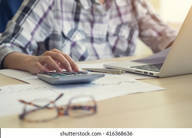 Businessman using a calculator to calculate the numbers in a office