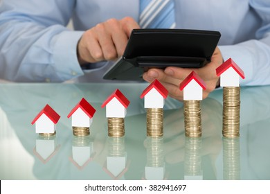 Businessman Using Calculator In Front Of Stacked Coins And House Models