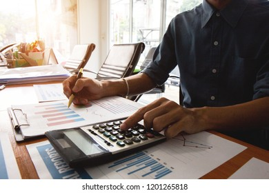 Businessman using calculator and holding money for calculate tax in office.concept