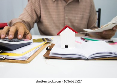 businessman using calculator and holding pen on tax paper in office.Accountingconcept.
