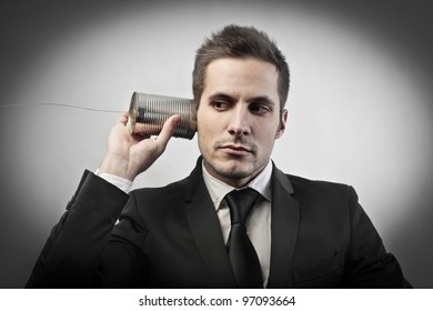 Businessman using a can and a rope as a telephone