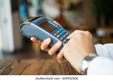 Businessman using cashless payment in cafe