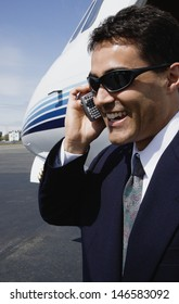 Businessman using cell phone next to airplane