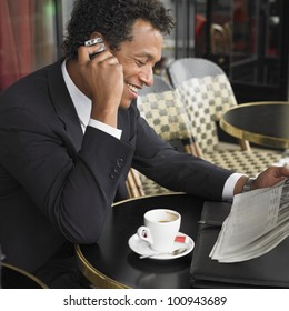 Businessman using cell phone at outdoor cafe