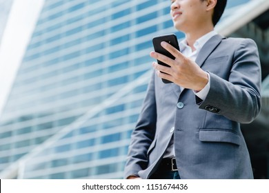 businessman using a cell phone, smiling. Taken in front of a modern office
