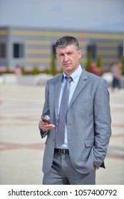 Businessman using cell phone while walking on path outside offic