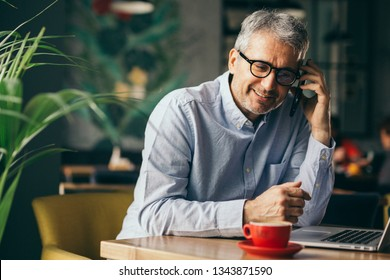 businessman using cellphone in cafeteria on coffee break