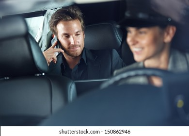Businessman using cellphone in limousine, female chauffeur driving.