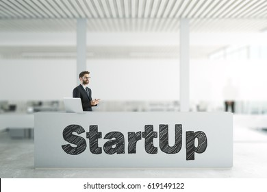 Businessman using cellphone at reception desk with startup writing. Entrepreneurship concept. 3D Rendering